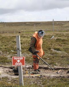 De-mining expert working in Falklands' peaty soil in search of minimum metal mines