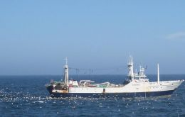 A trawler is followed by seabirds while discarding fish offal