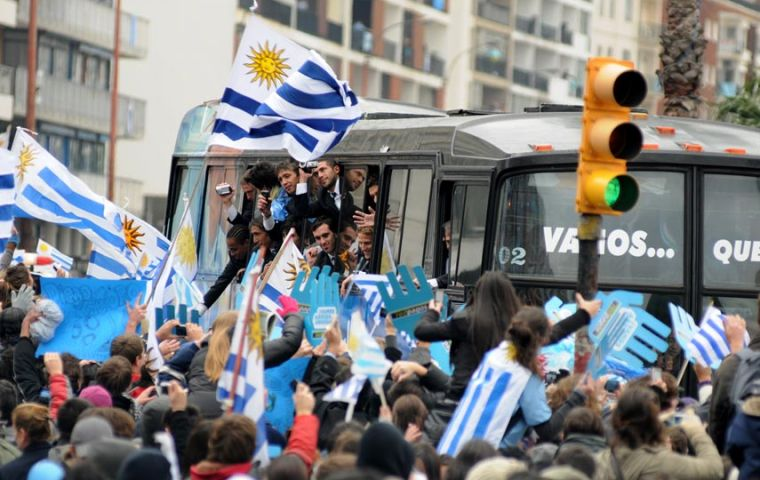 The bus with the team surrounded by a joyous crowd draped in flags