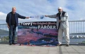 "The two activists raise a banner at the roof of the hotel ""Hafnia"" in front of the parliament of Faroe (WDSF/ProWal)"