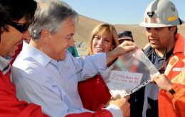President Piñera shows the cameras the written message from the trapped miners