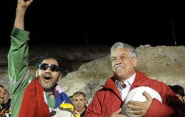 President Piñera  ® with the last miner to emerge and leader of the group Luis Urzua