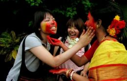 Korean women celebrating India's Holi festival and a young tourist backstage at the Chinese Opera Theatre, among the five best expressions