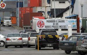 A view of the entrance to the cargo section of the Argentinian port of Ushuaia, with a sign that reads; English pirate ships are prohibited from mooring.