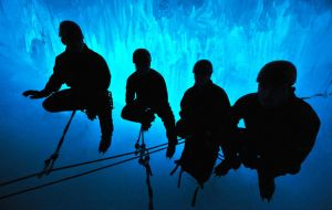 The Royal Marine and BAS explorers are silhouetted against the stunning natural colours of the ice cavern
