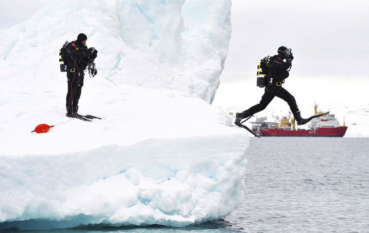 Taking the plunge: A navy diver leaps from an iceberg near the Antarctic Peninsula, while a colleague looks on (Photo: Arron Hoare/MoD)