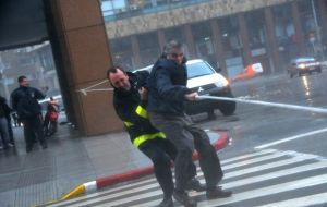 Firemen help pedestrians cross the streets with a rope line