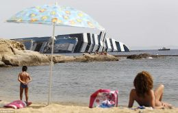 The Costa Concordia still lies next to the rocky outcrops off Giglio Island (Photo Daily Mail)