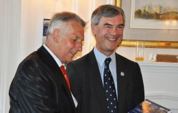 Patrick Watts MBE gives a copy of his book to Falklands Governor Mr. Nigel Haywood CVO