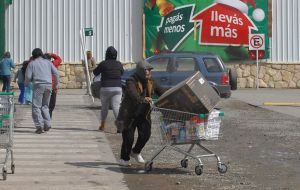 Looters loaded with electronic appliances flee from the supermarket