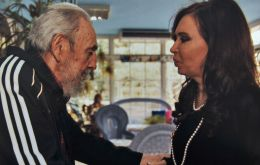 The Argentine president holds hands with the ailing Fidel Castro