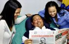 Hugo Chavez and his daughters, as he holds a copy of Cuba's state newspaper Granma in Havana, Cuba, Thursday, Feb. 14.2013