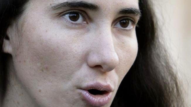 Yoani Sanchéz, blogueira cubana, de perfil com a boca aberta durante uma fala e olhar compenetrado