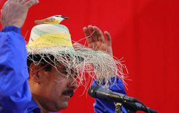 Maduro campaigning with his famous hat and the spirit of Chavez represented in a bird