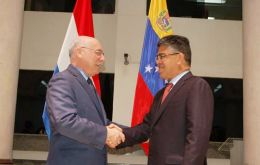 The two ministers with the background of the two flags shake hands in Asunción