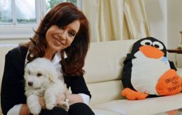 Cristina Fernandez holding the pup Simon, a gift from Hugo Chavez brother Adan and next to a giant penguin sent by a well wisher
