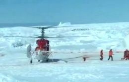 The Snow Dragon helicopter lands next to Akademic Shokalskiy to pick up the passengers