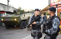 Heavy armed soldiers patrol the streets while people get on with their daily business