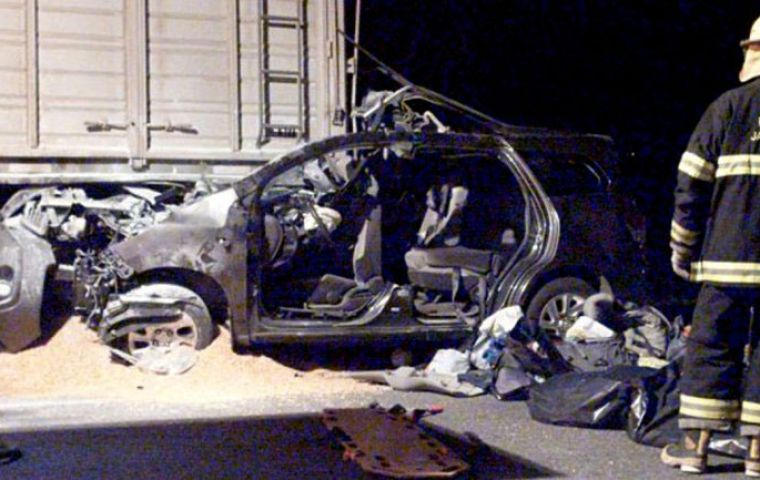The remains of the car that crashed into a grain truck and caught fire