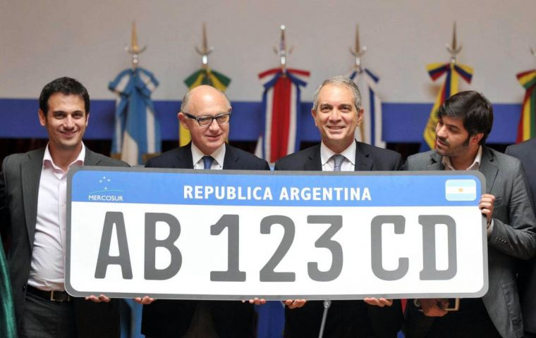 Timerman and other officials hold the enlarged prototype of the Mercosur cars' number plate