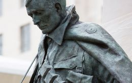 The Memorial is a bronze statue of a British soldier standing in front of an inscribed and carved obelisk of Portland stone on a base of Welsh slate