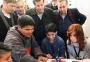 The Argentine president at the Villa 20 township school watching children manipulate car model robots