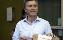 An enthusiastic Macri at the voting station before depositing the ballot for the awaiting media