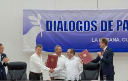 Castro handed the document to Colombian President Juan Manuel Santos and FARC chief Rodrigo Londoño, who shook hands amid applause.