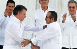 Colombian President Juan Manuel Santos and FARC commander Rodrigo Londoño, Timochenko, formally ended the long and brutal war, then shook hands.