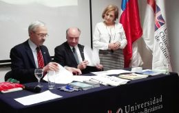 MLA Dr. Elsby signs the MOU with Pedro Pfeffer, (center) President of the Executive Council, while UCBC Vice-Chancellor Maria Cristina Brieba looks on.
