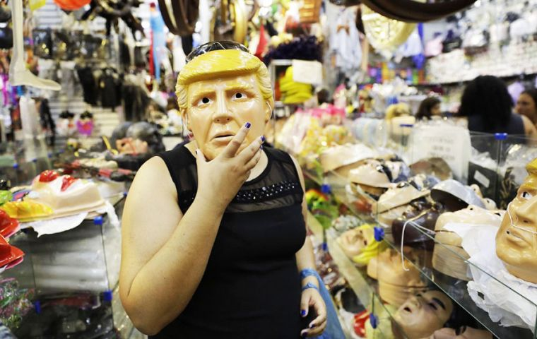 With his blond hair and his orange-tinted face, a Trump mask is prominently featured in the display window of an enormous store selling all sorts of costumes