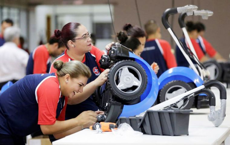 "Dark-blue electric scooters assembled by 20 workers at the Estrela factory, known as a ""maquila"", will be shipped across the Paraguay border to Brazil"