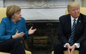 "In the video, Merkel can be seen saying: ""do you want to have a handshake?"" Trump turns and looks at her but continues sitting in the same position."
