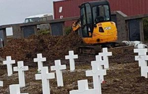 Some of the pictures show the removed graves and a small excavator at the cemetery