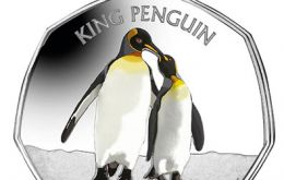 The seven-sided coin with a vivid color application features a large, adult male king penguin with his smaller female companion lovingly touching their beaks.
