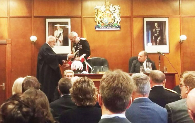 Governor Phillips CBE during the Oath of Allegiance ceremony at the Court and Assembly Chamber receives the ceremonial sword from the Speaker of the House Keith Biles