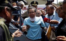 Fujimori lay propped up on a hospital bed wearing a white gown, with a blood pressure cuff on his right arm and another monitor clasped to his left index finger.