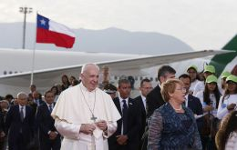 Francis was greeted by President Michelle Bachelet and a band played while the two walked on a red carpet as night began to fall.