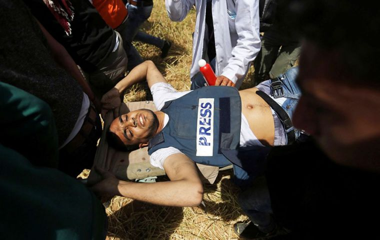 "Yaser Murtaja wounded wearing a vest with the word ""press"". He worked as a photographer for the Ain Media agency, based in Gaza. Photo: Ibraheem Abu Mustafa / Reuters"