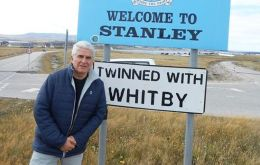 Jorge Lidio Viñuela during a visit to the Falkland Islands, pictured at an iconic signboard at the entrance of Stanley