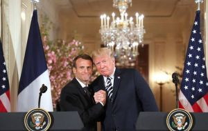 Trump held Macron's hands, showered him with compliments and even brushed what he said was a piece of dandruff off of Macron's suit.