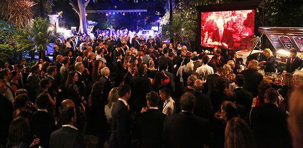 Los invitados a los jardines de la residencia siguen el discurso del embajador Mark Kent en una de varias pantallas