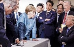 German Chancellor Merkel in an assertive pose planting both hands firmly on a table as she addresses an emotionless US president Trump