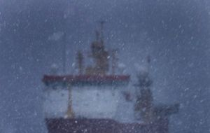 Ice Patrol HMS Protector in Antarctica under heavy snow and surrounded with penguins at Port Lockroy