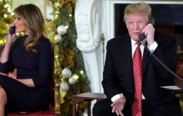 Donald Trump and his wife Melania were taking calls from American children as the couple sat under two gargantuan Christmas trees