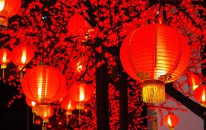 Red Chinese lanterns hang in streets; red couplets are pasted on doors; banks and official buildings are decorated with red New Year pictures depicting prosperity