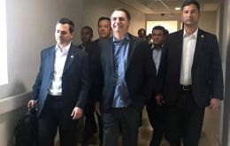 A photo posted by his office showed Bolsonaro smiling as he walked down a corridor with officials in tow.