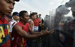 "At least four people died in clashes between civilians and troops and armed groups, ""colectivos"" loyal to Mr Maduro, including a 14-year-old boy. (AFP)"