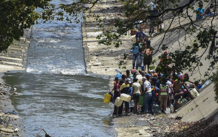 Dozens of people flocked to the Guaire river, which snakes along the bottom of a sharp ravine alongside Caracas' main highway, to fill up a 15-litre plastic container