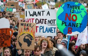 "Across the world placards inspired: ""Like the ocean, we will rise""; ""Our future in your hands""; ""System Change not Climate Change""; ""Don't be a Trump"""